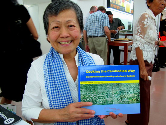 Narin Seng Jameson holds up her new cookbook, Cooking the Cambodian Way